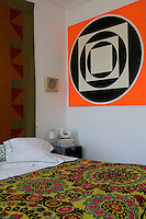 A corner of a modern bedroom with a brightly coloured patterned cover on the bed and apop-art painting and folk-art quilt hung on the walls
