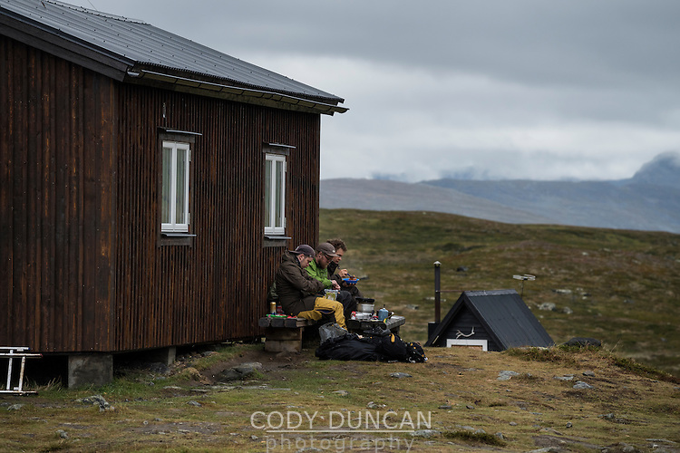 Group of hikers sit outside STF Sälka mountain hut, Kungsleden trail, Lapland, Sweden