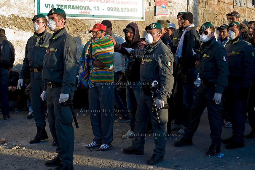 Immigrati Tunisini vengono scortati dalla Guardia di Finanza per l'identificazione prima di essere trasferiti nei centri di accoglienza. Tunisian immigrants are escorted by Guardia di Finanza police officers as they arrive at the southern Italian island of Lampedusa.