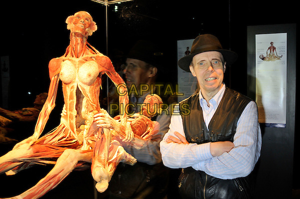 DR. GUNTHER VON HAGENS & THE SUSPENDED ACT.Press conference for the new sex plastinates which is part of the Body Worlds & the Mirror of Time exhibition at the O2 Arena, Greenwich, south-east London, England..June 23rd, 2009.bodyworks body works half length muscles internal organs flesh muscle skin models bone sexual position half length black hat blue shirt waistcoat arms crossed  .CAP/PL.Phil Loftus/Capital Pictures.