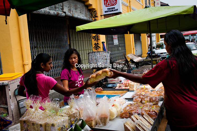Locals buy pastries from an open air street market in the UNESCO heritage city of Georgetown in Penang, Malaysia. Photo: Sanjit Das/Panos