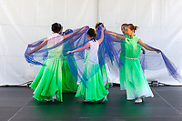Girls wearing green dresses dancing Chinese Blue Vail Dance, Northwest Folklife Festival 2016, Seattle Center, Washington, USA.