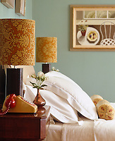 A retro telephone stands on the bedside table beside a lamp with a lampshade covered in vintage flock