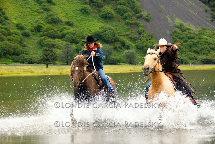 Cowgirls racing their horses across the Pasagshak River on Kodiak Island, Alaska