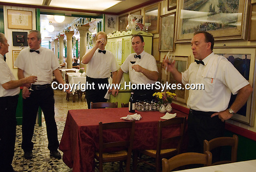 Venice Italy 2009. Interior restaurant waiters sampling dinner guests wine.