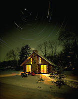 Light swirls of star patterns above the cozy glow of a cabin in winter.