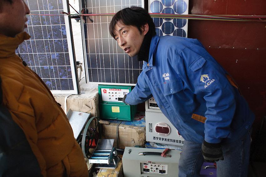 Mr Guo présente une batterie pouvant être associée aux panneaux solaire, Xiahe, decembre 2009.