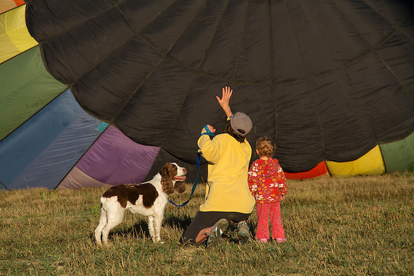 Mother, child and dog look at a hot air balloon, Boulder, Colorado, USA.