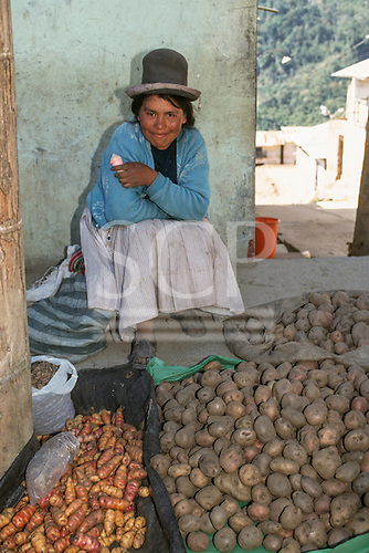 Peru. Aymara woman selling three varieties of potatoes and a small bag of Chuño freeze-dried potatoes. She is smiling and holding a typical pink Peruvian commercial sweet cone.