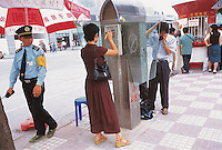 People use public phones in Guangzhou, China..