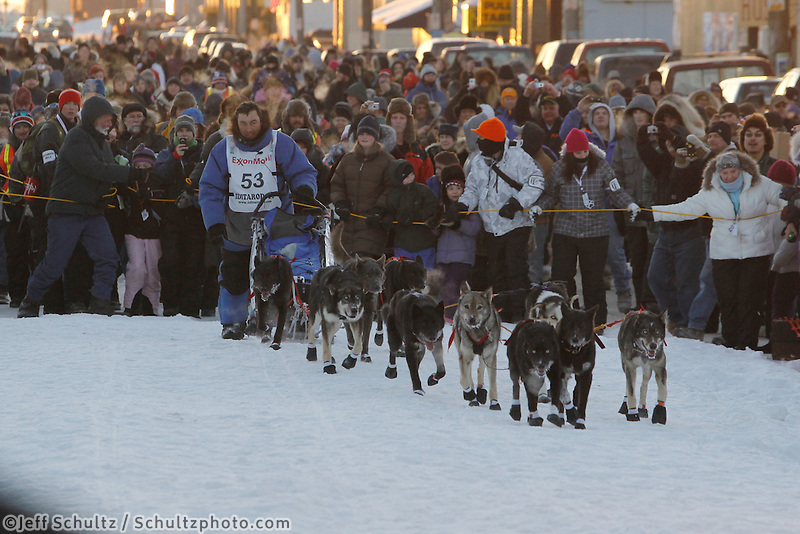 John Baker runs into the finish chute with a crowd gathered behind in Nome as he wins the 2011 Iditarod .