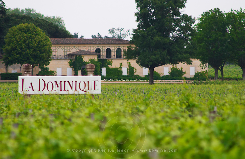 A sign in the vineyard saying Chateau La Dominique, and a unknown winery in the background. Could be La Dominique but not certain. Saint Emilion Bordeaux Gironde Aquitaine France
