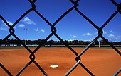 Florida, USA. Red baseball diamond with white batting plate and green grass beyond in Harry Harris County Park, Key Largo.
