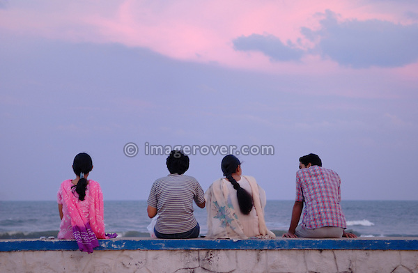 Group of Indian people relaxing after sunset at Chennai beach. India, Tamil Nadu, Chennai (Madras).  No releases available.