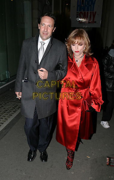 JOAN COLLINS & PERCY GIBSON.leaving When Harry Met Sally play at the Theatre Royal, Haymarket.19 February 2004.full length, full-length, long red satin coat.www.capitalpictures.com.sales@capitalpictures.com.© Capital Pictures.