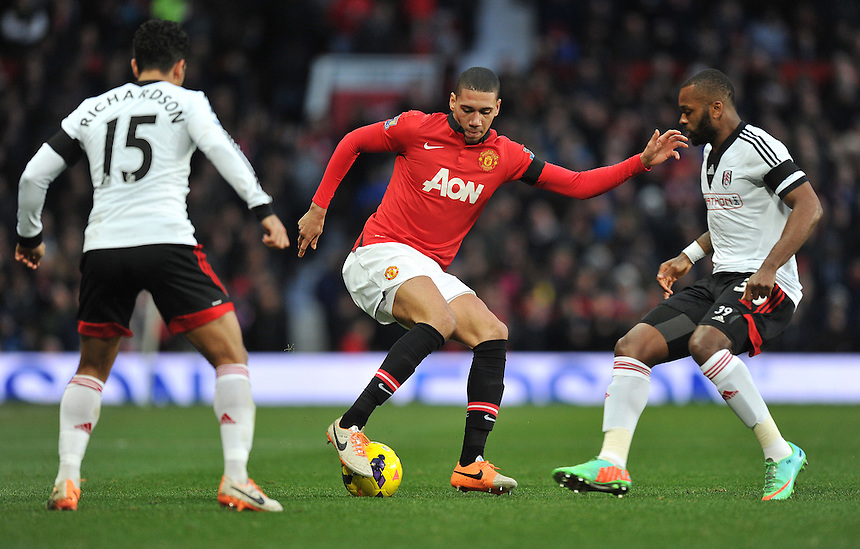 Manchester United's Chris Smalling flanked by Fulham's Kieran Richardson (left) and Darren Bent (right)<br /> <br /> Photo by Dave Howarth/CameraSport<br /> <br /> Football - Barclays Premiership - Manchester United v Fulham - Sunday 9th February 2014 - Old Trafford - Manchester<br /> <br /> &copy; CameraSport - 43 Linden Ave. Countesthorpe. Leicester. England. LE8 5PG - Tel: +44 (0) 116 277 4147 - admin@camerasport.com - www.camerasport.com