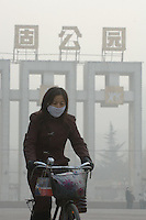 A resident of Lanzhou city struggle through the heavily polluted streets on a bicycle. Lanzhou is the most polluted city in China and is said cannot be seen from a satellite due to the pollution many of the residents wear face masks for protection..22 Nov 2005