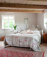A red rug and dashes of pink on the quilt bring warmth to the pale colour scheme of this bedroom