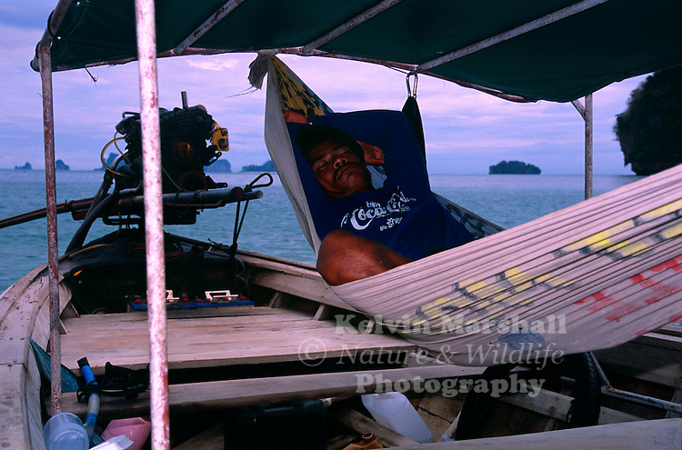 Thai boat captain sleeping in his Hammock aboard his boat. Krabi province, Thailand.