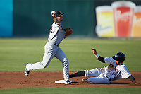 Justin Jacobs (12) of the Hickory Crawdads makes a throw to first base as Michael Hickman (18) of the Kannapolis Intimidators slides into second base at Kannapolis Intimidators Stadium on May 2, 2018 in Kannapolis, North Carolina.  The Intimidators defeated the Crawdads 9-6.  (Brian Westerholt/Four Seam Images)