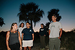 Mark Dodd (right), State Sea Turtle Program Coordinator of the Georgia Department of Natural Resources, waits with Bonnie Berry and Denise, both of University of Georgia, as well as Sarah Dubose (back in white) and Sarah Rose (back navy), a sea turtle technician, for the tide to recede before the start of a night of searching, tagging, and gathering data from nesting sea turtles on Ossabaw Island, Georgia, June 17 and 18, 2012.
