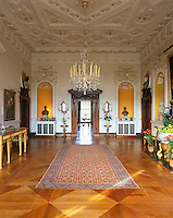 A long hall with marquetry floor and ornate plasterwork ceiling
