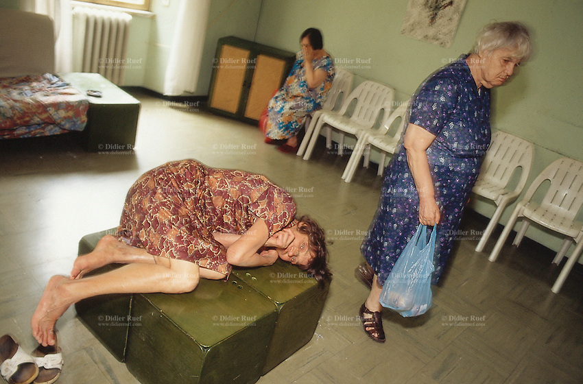 Italy. Province of Lazio. Rome. Santa Maria della Pieta is an asylum for mentally handicapped people. A bare feet woman lays on wooden bricks while another woman carries in her hand a blue plastic bag. A third person is sitting on a white plastic chair. Mental hospital. Lunatic asylum. Psychiatric hospitals, also known as mental hospitals, are hospitals specializing in the treatment of serious mental disorders. Santa Maria della Pieta is specialised in the temporary or permanent care of residents who, as a result of a psychological disorder, require routine assistance, treatment, or a specialised and controlled environment. Patients are often admitted on a voluntary basis, but involuntary commitment is practiced when an individual may pose a significant danger to themselves or others. 10.07.97 © 1997 Didier Ruef
