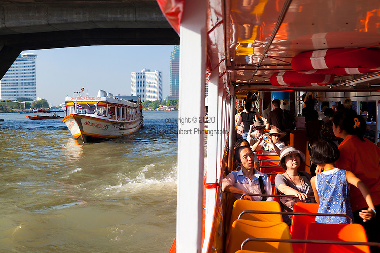 Traveling by boat down the Chao Phraya River through downtown Bangkok, Thailand,  The Orange Flag Express Boat is used by tourists and locals alike.