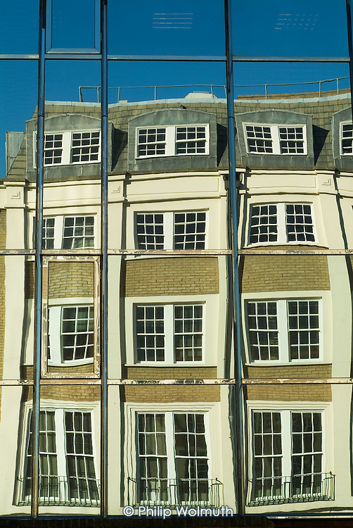 Victorian office building reflected in the mirrored cladding of a modern block in Euston, London.