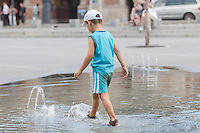 Child cools itself down in a public fountain in the summer heat in Budapest, Hungary on August 21, 2012. ATTILA VOLGYI