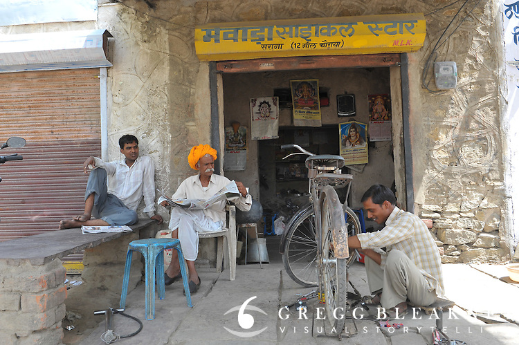 A client reads the morning paper while his bicycle is being repaired.  Rajasthan, India.