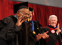NWA Democrat-Gazette/ANDY SHUPE<br /> Judge L. Clifford Davis (left) waves to the audience Saturday, May 13, 2017, alongside James Coleman, provost of the University of Arkansas, and Ben Hyneman, chair of the Board of Trustees of the University System, before Davis is awarded an honorary degree during commencement exercises in Bud Walton Arena in Fayetteville. Visit nwadg.com/photos to see more photographs from the ceremony.