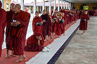 Myanmar, Burma.  Buddhist Monks Lined up to Receive Charitable Gifts from Wealthy Donor, Alodaw Pauk Pagoda, Nampan Village, Inle Lake, Shan State.