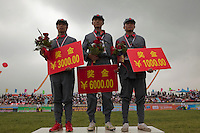 Winning competitors dressed in PLA (People's Liberation ARmy) revolutionary era outfits receive their prizes on the podium at the Red Games. Held in Junan County, this sporting event is a nostalgic tribute to the communist era.