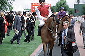 Horses and jockeys parade around the Paddock before the Derby at Epsom Downs racecourse.
