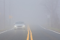Single car driving on a rural road through thick fog with plenty of copy space