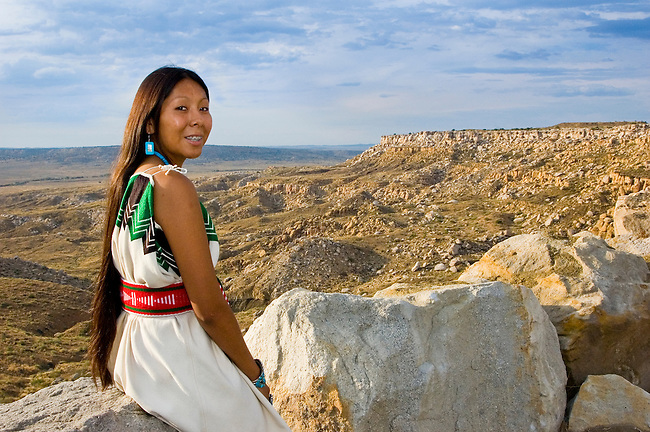 Traditional Hopi girl, Povi Lomayauma 16 year old teenager, dressed in traditionally woven cotton dress sits on a rock outcrop overlooking her ancestral lands and Hopi Indian Reservation from the ancient town of Tewa located on the First Mesa near Polacca Arizona