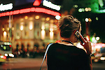 Female on telephone in street at night