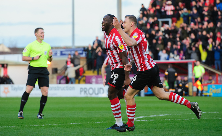Lincoln City's John Akinde, left, celebrates scoring the opening goal with team-mate Harry Anderson<br /> <br /> Photographer Chris Vaughan/CameraSport<br /> <br /> The EFL Sky Bet League Two - Lincoln City v Newport County - Saturday 22nd December 201 - Sincil Bank - Lincoln<br /> <br /> World Copyright © 2018 CameraSport. All rights reserved. 43 Linden Ave. Countesthorpe. Leicester. England. LE8 5PG - Tel: +44 (0) 116 277 4147 - admin@camerasport.com - www.camerasport.com
