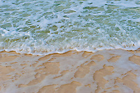 Closeup of small ocean waves over beach.