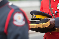 A member of the RCMP holds a hat during a parade commemorating police officers fallen on duty Sunday September 26, 2010.