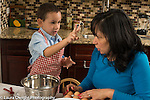 3 year old boy in kitchen at home with mother learning to cook baking, holding up two fingers to mother showing the number of eggs to go in the batter