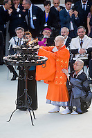 Assisi,Italy, September 20, 2016. Il buddista Giapponese Koei Morikawa, accende una candela al termine delle celebrazioni della giornata di preghiera per la Pace ad Assisi. Japanese Buddhist Koei Morikawa, left, is assisted as he lights a candle during the closing event of an inter-religious prayer gathering, in front of the Basilica of St. Francis, Assisi. War refugees and leaders and representatives of several religions, including Christians, Jews, Muslims, Hindus and others, joined Pope Francis in a day of prayer for peace in Assisi, the hometown of St. Francis, who preached tolerance and gentleness.