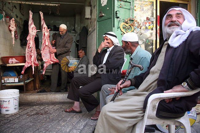 Palestinian men sit outside a butcher shop as they wait to buy meat in the old city of the West Bank city of Hebron  on November 15, 2010, ahead of the Muslim holiday of Eid al-Adha or Feast of the Sacrifice, which marks the end of the annual hajj or pilgrimage to Mecca and is celebrated in remembrance of Abraham's readiness to sacrifice his son to God. Photo by Najeh Hashlamoun