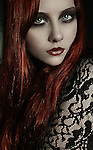 A portrait of a girl with dark make up and red hair wearing black lace clothing