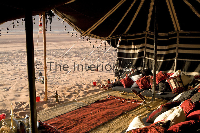 Scattered cushions and floor-level seating in the tent with a view out over the surrounding desert