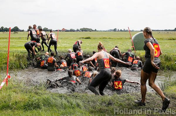 Nederland Schermerhorn 2016 07 10 . De jaarlijkse Prutmarathon door de modderige slootjes van de Mijzenpolder. Mensen helpen elkaar de sloot uit. Foto Berlinda van Dam / Hollandse Hoogte