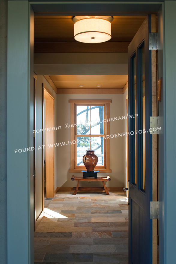 An open front door welcomes visitors into a tiled front entry hall.