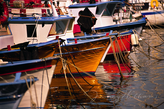 Wooden boats are docked in a small Italian harbor off the Mediterranean Sea