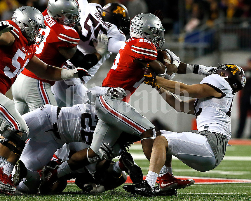 Ohio State Buckeyes running back Ezekiel Elliott (15) is taken down by Minnesota Golden Gophers linebacker Cody Poock (12) in the first half of their game at Ohio Stadium in Columbus, Ohio on November 7, 2015. (Columbus Dispatch photo by Brooke LaValley)